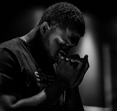 Black man praying - photo by Jack Sharp on Unsplash